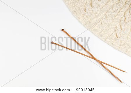 Knitting and pair of wooden knitting needles on white background. Top view