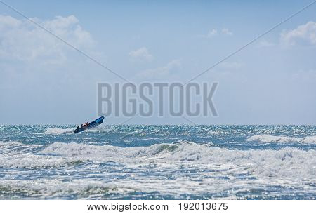 The blue motor boat hurries with rescue team to the aid overcoming big waves of the raging sea.