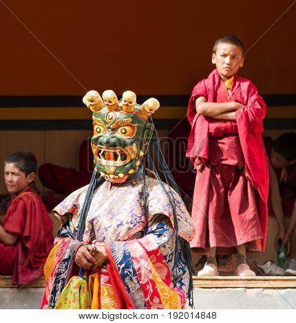 Lamayuru India - June 17 2012: monk performs a religious masked and costumed mystery dance of Tibetan Buddhism and children monks carefully watching the ritual during the Cham Dance Festival in the Lamayuru monastery India.