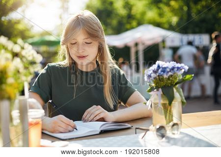 Portrait of a young business woman or student writing her plans in notepad talking on a smartphone planning a blog post during a luch break in park on a sunny summer day.