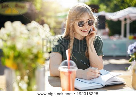 Portrait of a young business woman or student writing her plans in notepad talking on a smartphone smiling wearing glasses during a luch break in park on a sunny summer day. Education concept