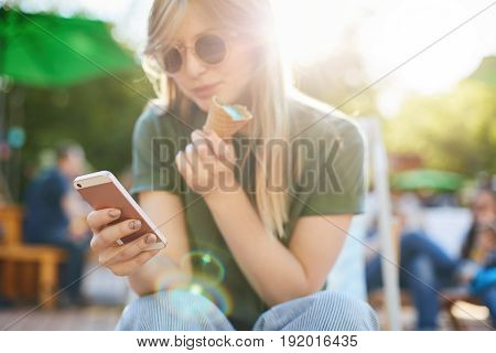 Woman eating icecream using smartphone. Portrait of a girl with ice cream browsing through social media or messaging her friends enjoying summer in the city park wearing glasses. Focus on phone.