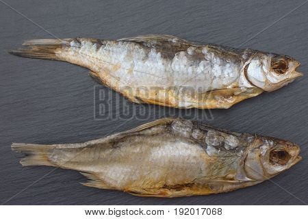 Two Dried Salted Roach On Black Background Of Slate Or Stone.
