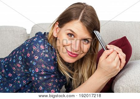 Picture of a beautiful young woman lying on the couch holding her mobile phone having a video chat