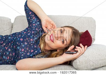 Picture of a seductive young woman lying on the couch holding her mobile phone