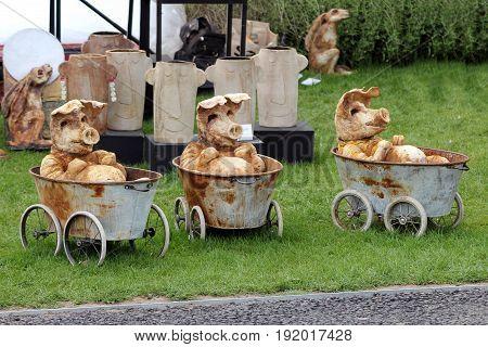 Three Ornamental Pottery Pigs In Bathtubs On Wheels, At A Craft Fair