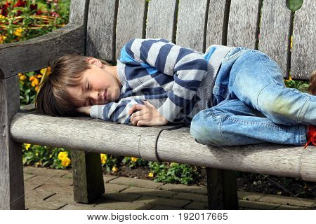 Young boy asleep on a wooden park bench