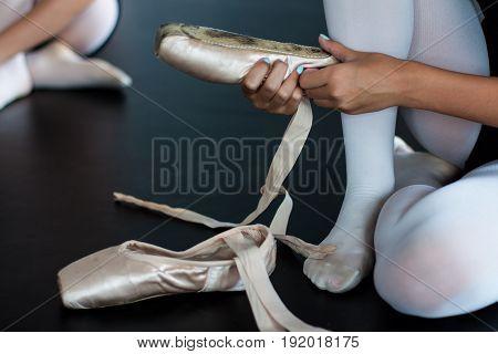 Ballet dancer is checking her ballet shoes