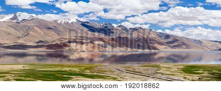 Tso Moriri mountain lake and the mountain river floodplain panorama in the Himalayas with fantastic reflections of the mountains and sky in the lake (Ladakh northern India)