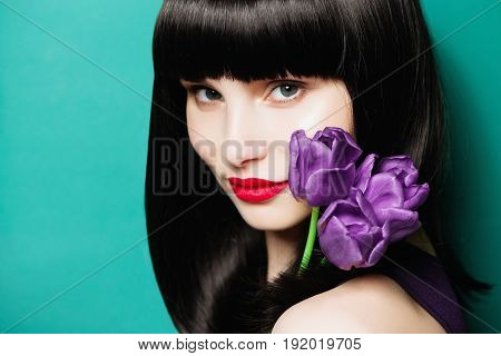 Portrait of a beautiful brunette woman with a lilac tulip on a blue background