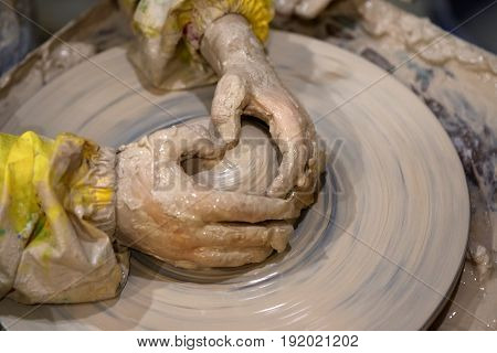 Hands Of Young Girl In Process Of Making Clay Bowl On Pottery Wheel
