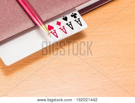 A solid pen on a brown diary with a winning combination on a wooden background four aces mean success