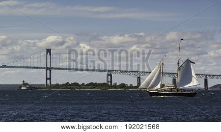A view of a two-master yacht sailing in front of the Newport Bridge and Rose Island Lighthouse Rhode Island