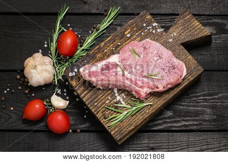Piece of raw pork loin on old cutting board vegetables herbs and spices on dark wooden background. Meat prepared for cooking