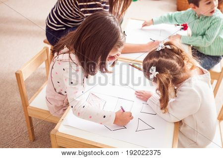 Overhead view of children in kindergarten learn letters and shapes coloring them