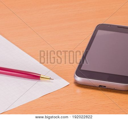 Business still life accessories on a wooden background black mobile phone pen for writing and blank sheet