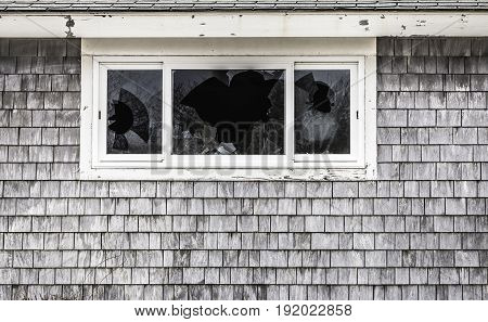 Close-up of broken windows with cedar shingle surround abandoned building copy space