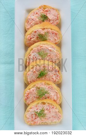 Smoked salmon and cream cheese on cibatta rounds appetizers in vertical format. Shot in natural light. from overhead.