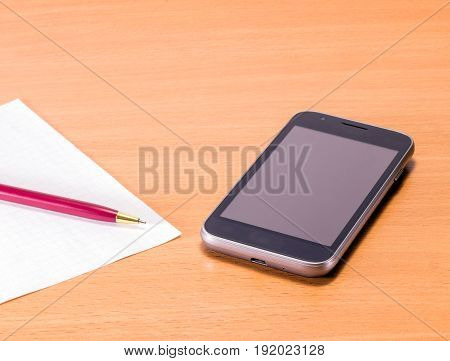 Accessories for business people on a wooden background black compact smartphone solid writing pen and blank sheet
