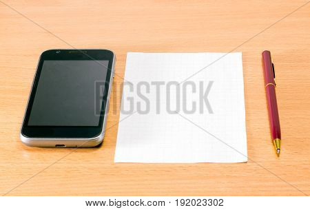 Phone pen and clean sheet on a wooden background accessories for business people are solid and necessary
