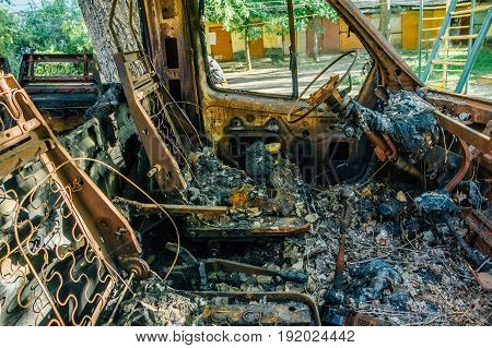 Burned out car, inside view, rusty steering wheel