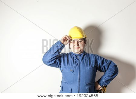 Smiling female worker dressed in work clothes, holding a yellow helmet and yellow gloves