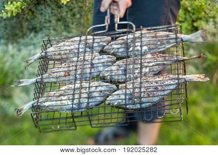 Man holding grilled fish in a steel grid