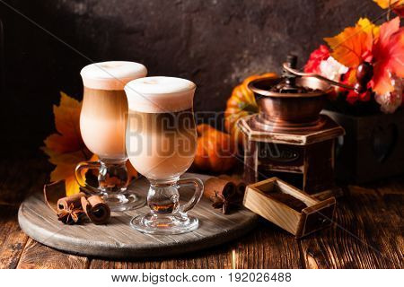 Two glasses pumpkin spicy latte with whipped cream and cinnamon on a wooden stand