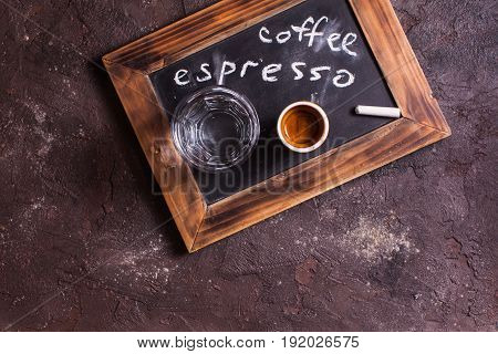 Top view of a cup of coffee and glass water on an old school slate with inscription