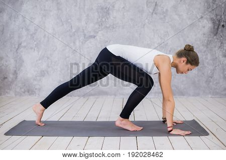 Beautiful young woman working out indoors, doing yoga exercise in the room with white walls, downward facing dog pose, adho mukha svanasana sun salutation pose, full length, side view.
