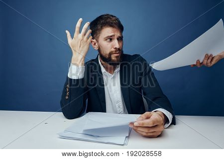Businessman is surprised, businessman with documents, businessman is working on blue background.