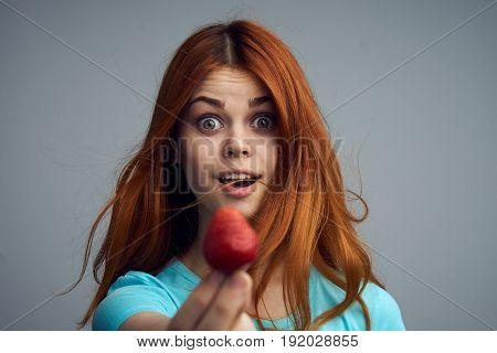 Happy woman holding a strawberry, woman with a strawberry on a gray background.