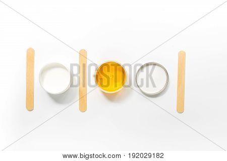 Concept depilation with wax and sticks on white background top view copyspace.