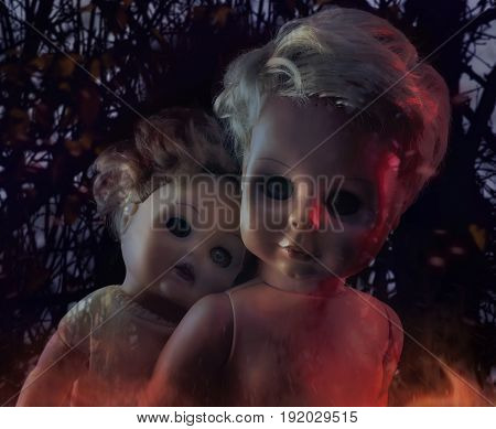 Horror dolls photo. Two burning creepy ghost dolls on mystic nature background photo.