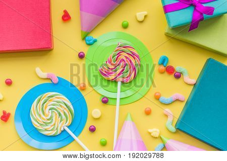 Birthday concept with wrapped gifts, greeting cards and sweets on yellow background top view .