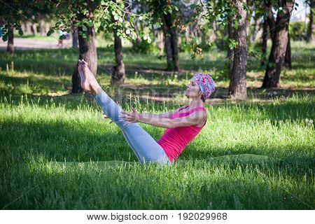 Young Woman Doing Yoga And Gymnastics In The Park. Boat Pose