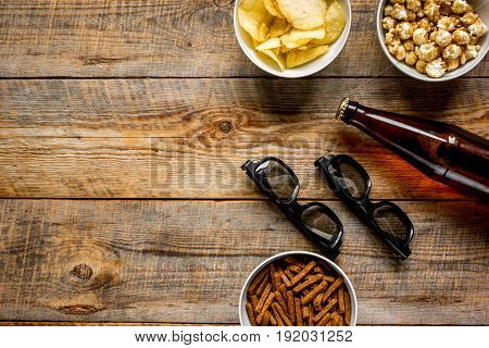 film whatching party with beer, crumbs, chips and pop corn on wooden background top view mockup