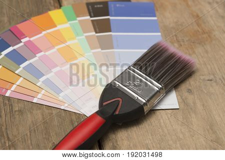 Two-inch Paintbrush And Paint Swatches On Wood