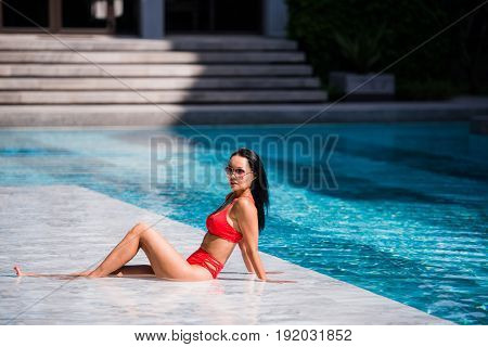 Teasing young smiling woman brunette beauty with red bikini rests laying on wet poolside marble enjoying summer in the outdoor swimming pool. Lifestyle, travel, freedom concept