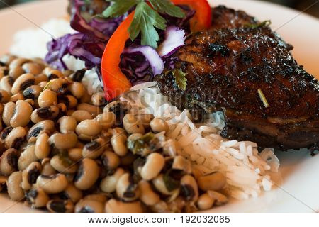 Jamaican jerk chicken served with rice and black-eyed peas