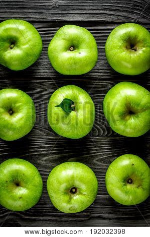 ripe green apples on dark wooden table background top view pattern