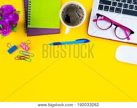 Flat lay top view office table desk frame. feminine desk workspace with office accessories including calculator mouse laptop glasses clips red pencil black coffee note book blue pen and pink flower on yellow background.