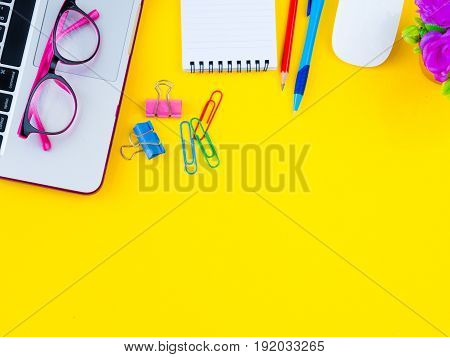 Flat lay top view office table desk frame. feminine desk workspace with office accessories including calculator mouse laptop glasses clips red pencil cutter note book blue pen and pink flower on yellow background.