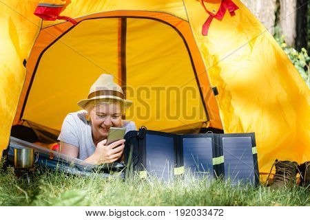 Woman Using Smartphone In Tent In The Woods.  Charges Using Solar Panels.