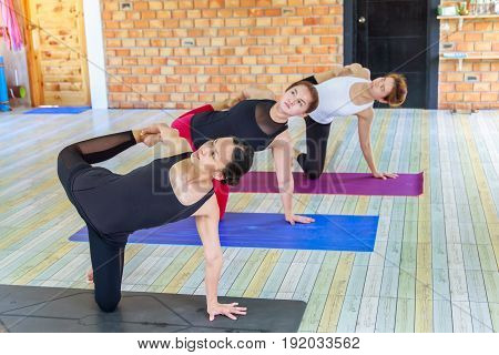 Fitness asian female group doing namaste yoga pose in row at the yoga class