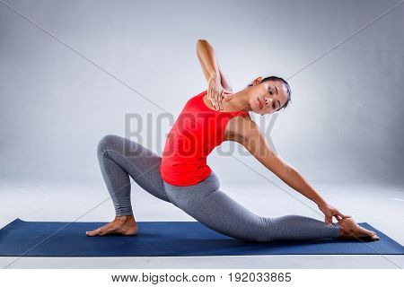 Yoga concept Pretty sporty indian woman smiling in doing yoga on concrete background.