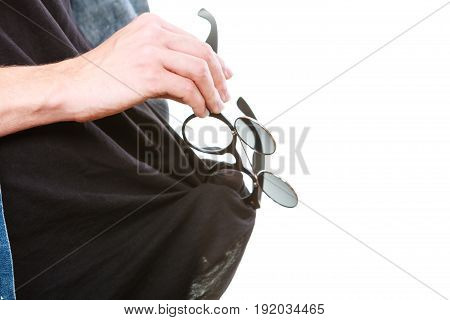 Cleanliness ophthalmology concept. Man cleaning glasses lens on black t shirt studio shot isolated.