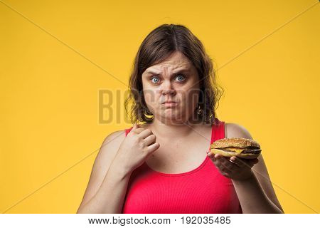 Woman with a hamburger, food, tasty, hamburger, woman on a yellow background.