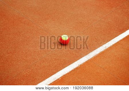 One red and yellow tennis ball lie on the tennis court. The concept of sport.