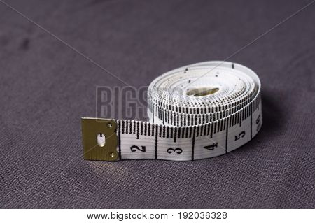 Inch, Centimeter Tape On A Background Of Grey Fabric
